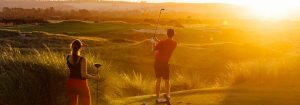 Couple playing golf at sunset.