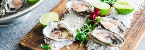Two oysters on a bed of salt, dressed with lime and ginger. An example of Barnbougle's Wine & Dine options.